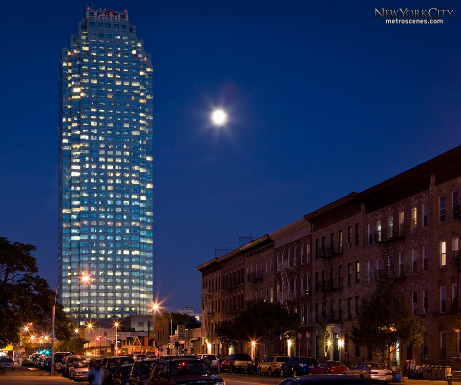 The moon shines next to the Citigroup Center in Queens.